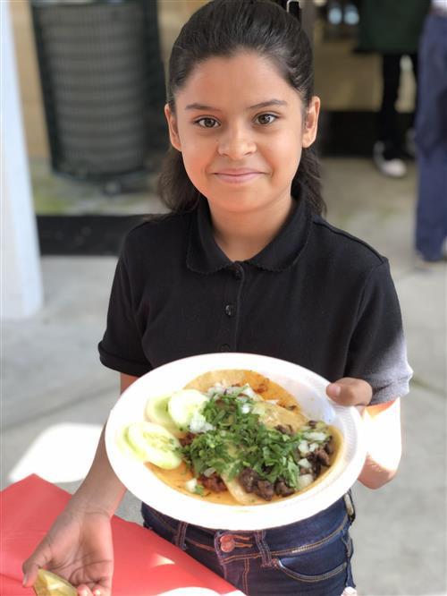 photo of Hispanic girl with plate of food