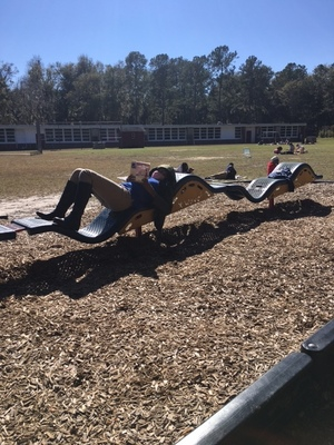 Students reading on playground equipment