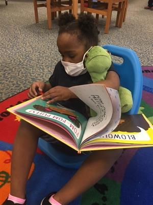 Student reading book to stuffed animal