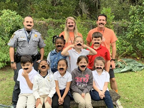 Group of 1st grade students, school resource officer, and teachers with mustaches on their faces