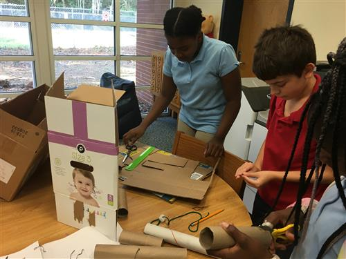 Students using cardboard to create a castle.