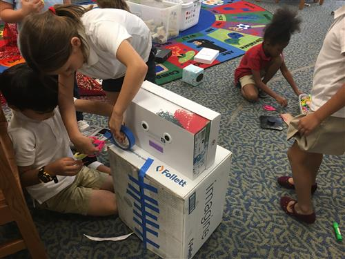 Students making a cardboard robot.