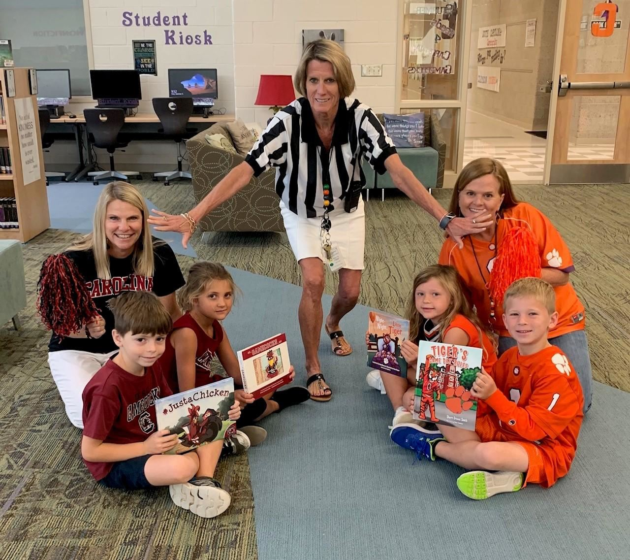 Ms. Felder helps referee the Big Game Reading Rivalry at Jennie Moore! What team are you reading fo