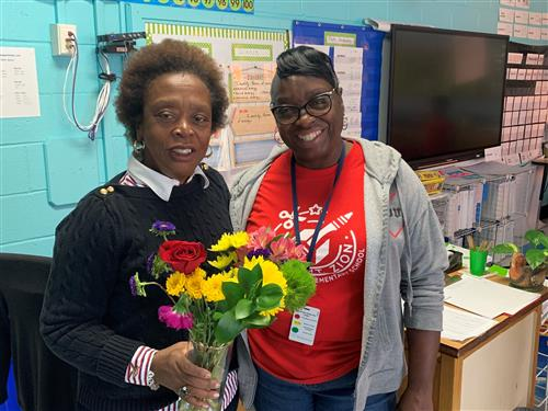Ms. Fordham presents flowers to Ms. Green